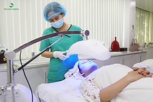 Kỹ thuật viên Thu Cúc Clinics đang chiếu ánh sáng BlueLight cho khách hàng.