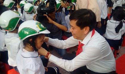 Bí thư T.Ư Đoàn, Chủ tịch Hội đồng Đội T.Ư Nguyễn Long Hải tặng mũ bảo hiểm cho học sinh tại trường Tiểu học Dịch vọng B, Cầu Giấy.