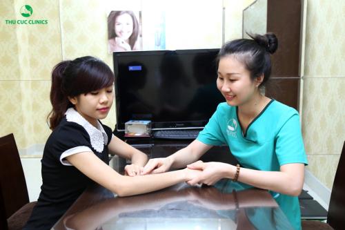 Chuyên viên tại Thu Cúc Clinics đang thăm khám tình trạng lông tay của khách hàng